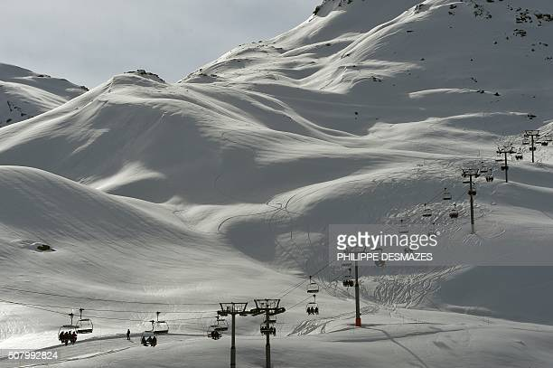 Skiers ride a chairlift on February 2 2016 in the French ski resort of Meribel in the 3 Valleys ski area the world's largest ski area in central...