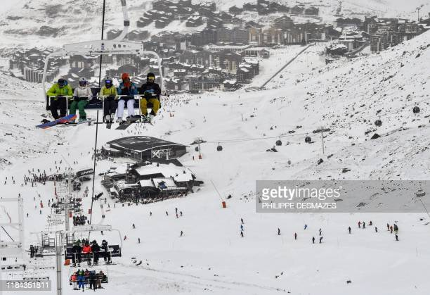 Skiers ride a ski lift above a slope at Val Thorens in the French Alps on November 24 during the ski station's opening weekend The kickoff of the ski...