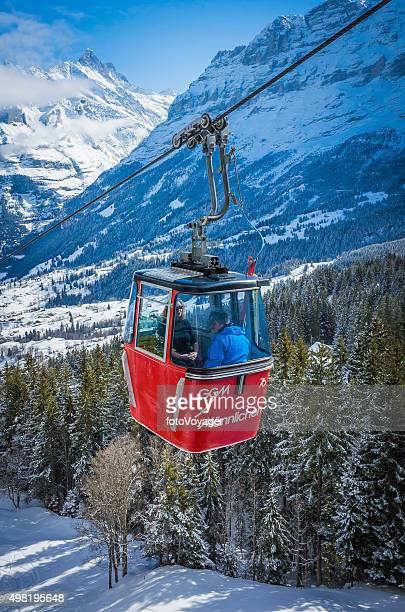 Skiers riding cable car above snowy Alpine mountain forests Switzerland