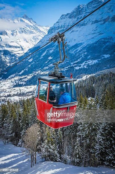 skifahrer fahren mit der seilbahn über schneebedeckte berge, alpine wälder, schweiz - gondel stock-fotos und bilder