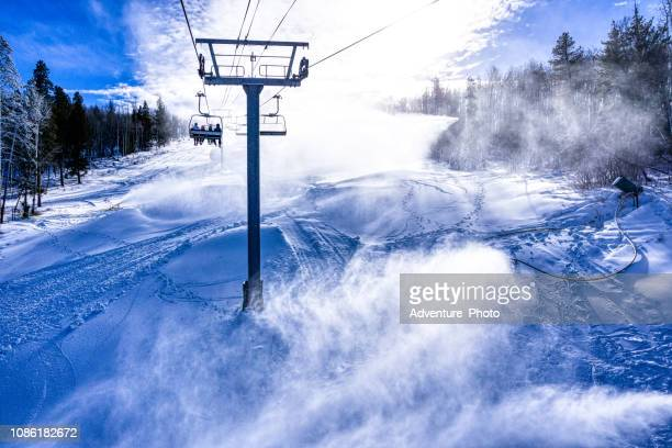 skiers riding chairlift with snowmaking - beaver creek colorado stock pictures, royalty-free photos & images