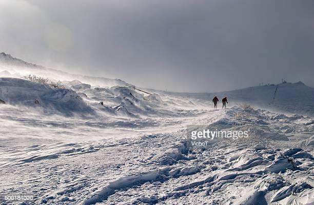Skiers'Silhouetten, die sich am Hang des Berges