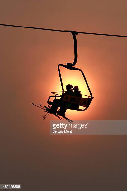 Skiers sit in a chairlift at sunset on January 23 2006 in Nanshan ski resort China In Nanshan Ski Resort the snow is manmade and each of the 12 runs...