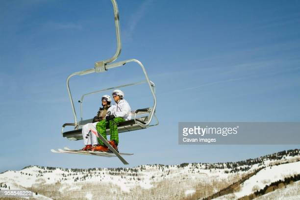 skiers sitting in ski lift against clear sky - ski lift stock pictures, royalty-free photos & images