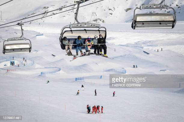 Skiers, some wearing protective face masks against the spread of the Covid-10 , ride a ski lift before hitting the slopes above the ski resort of...