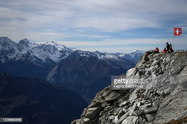 Skiers take a break next to a Swiss flag above the ski resort of Verbier in the Swiss Alps on November 15, 2020. - The coronavirus crisis shuttered...