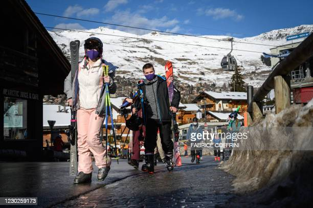 Skiers walk in the Alpine resort of Verbier, well known by British ski holiday makers, on December 22, 2020. - Switzerland on December 21, imposed an...