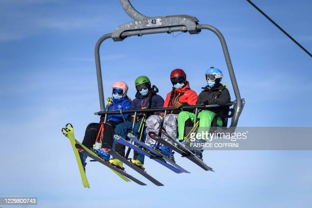 Skiers, wearing protective face masks against the spread of the Covid-10 , sit on a ski lift before hitting the slopes during the first snows of the...