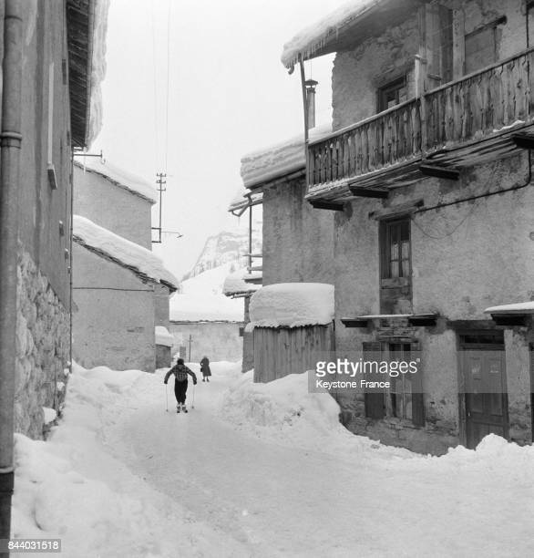 Skieur dans les rues enneigées du Val d'Isère France en février 1956