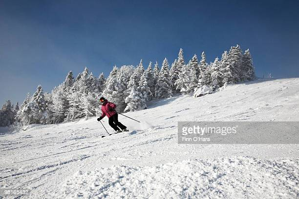 skiier heads down the run. - mont tremblant stock pictures, royalty-free photos & images