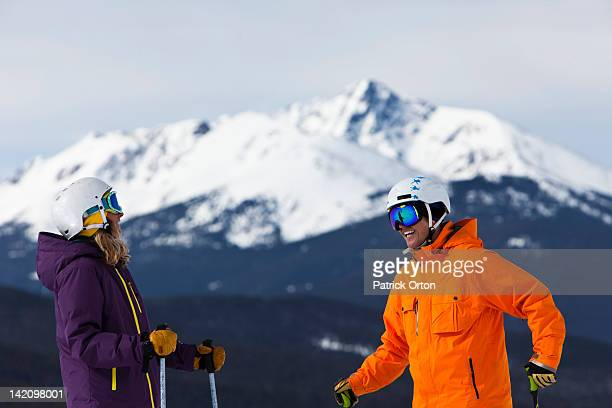A skiing couple laugh as they talk on a sunny day at Vail, Colorado.