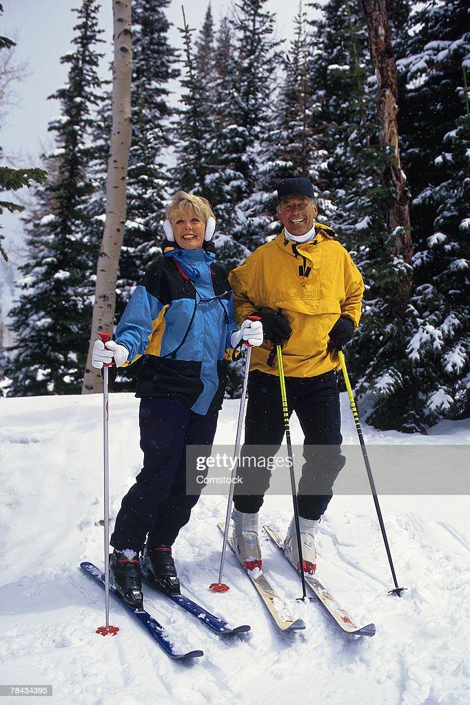 Skiing couple posing on the slopes : Stockfoto