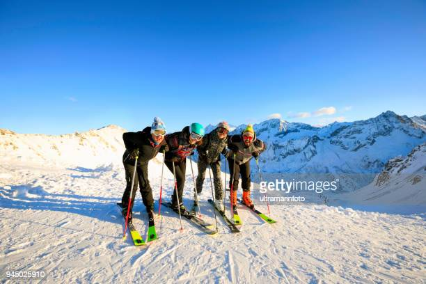 Skiing Happy skier class on the mountain top Amateur Winter Sports  alpine skiing. Group of skiers. Best friends men and women, snow skiers  enjoying on sunny ski resorts.  High mountain snowy landscape.