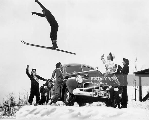 Man in the midst of a jump over a Chevrolet automobile while women around the car look on