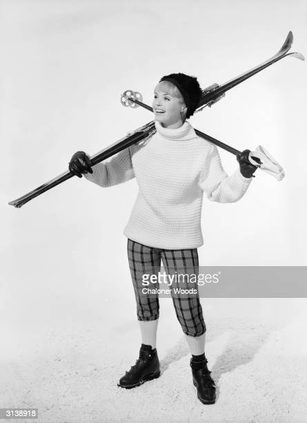 A skiing outfit consisting of polonecked sweater worn over kneelength largechecked trousers
