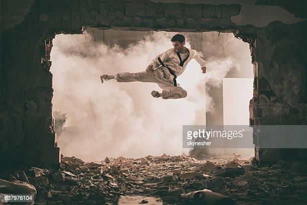 Skilful black belt martial artist performing fly kick.