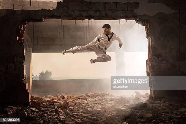 skilful martial artist performing jump kick among ruins. - taekwondo stock photos and pictures