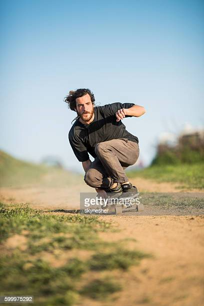Skilful young man riding a skateboard on a dirt road.