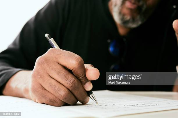 skilled black musician wrote a song made to the paper - form filling stock photos and pictures