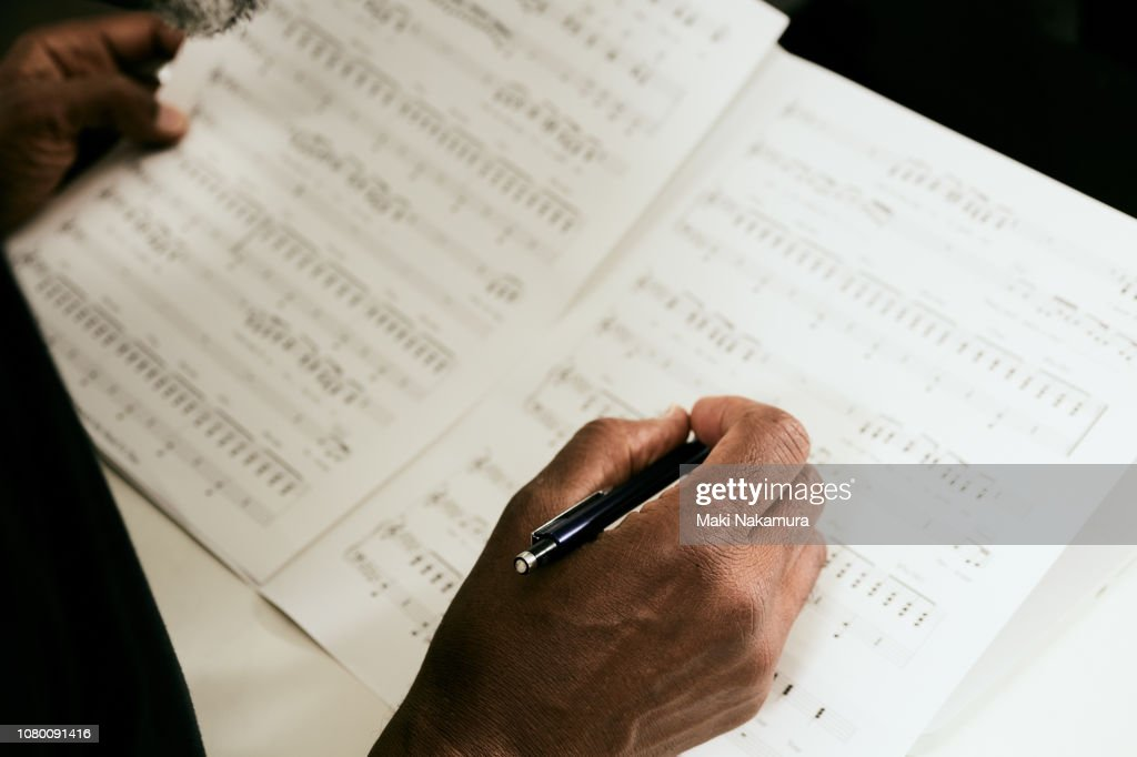 Skilled black musician wrote a song made to the paper : Stock Photo