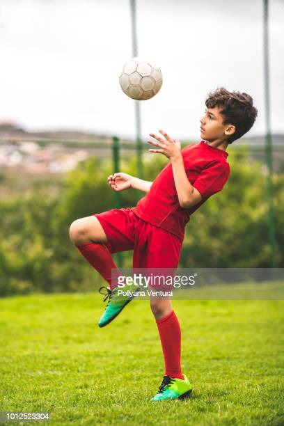 skilled boy playing soccer - kicking stock pictures, royalty-free photos & images