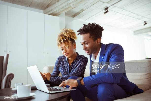 skilled corporate workers planning finance on sofa - izusek stock pictures, royalty-free photos & images