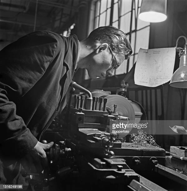 Skilled Czechoslovak operator uses a lathe to turn out Bren Gun parts at a munitions factory in England during World War II on 7th April 1941. The...