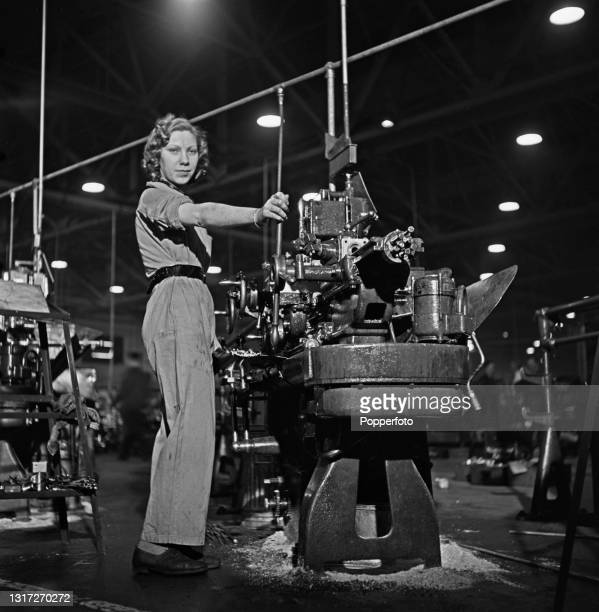 Skilled female munitions worker at work on her metal working lathe to produce parts for Supermarine Spitfire fighter aircraft at an aircraft factory...