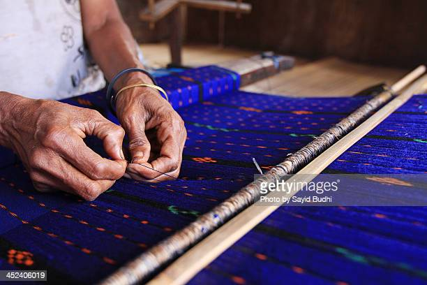 Skilled hands of woman working at the loom