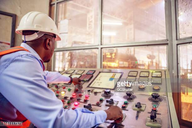 skilled machinery operator at a steel factory in africa - steelmaking stock photos and pictures