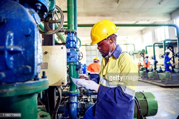 skilled machinery operators working at a factory in africa - africa stock pictures, royalty-free photos & images