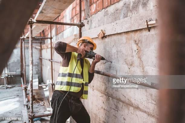 qualifizierte wartungsarbeiter am arbeitsplatz mit seinen bauwerkzeugen - bauarbeiter stock-fotos und bilder