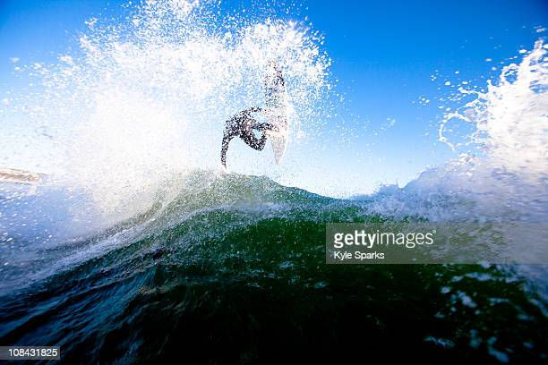 a skilled male surfer launches an air. - zuma beach stock photos and pictures