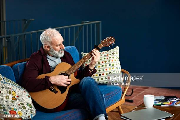 skilled musician sitting on sofa playing classical guitar - guitarist stock pictures, royalty-free photos & images