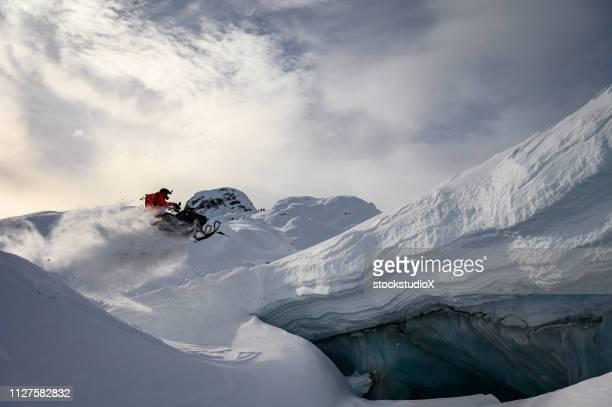 snowmobiler qualificado fazendo um salto nas montanhas - snowmobiling - fotografias e filmes do acervo