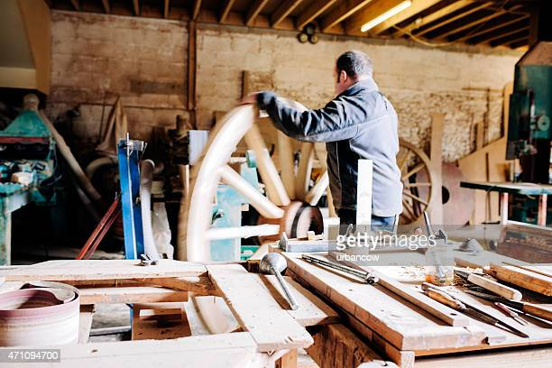 Skilled Wheelwright, in his workshop, rolls a wooden cartwheel