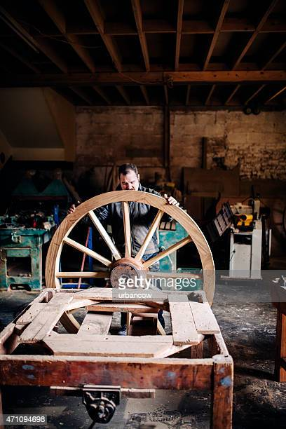 Skilled Wheelwright standing in his workshop with a wooden cartwheel