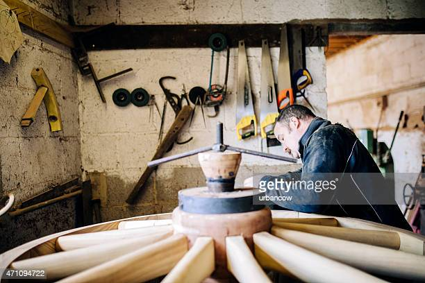 Skilled Wheelwright standing in workshop, working on a wooden cartwheel
