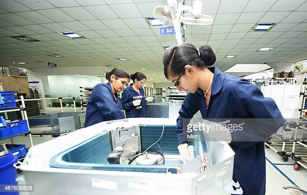 Skilled women workers assembling together air conditioners at united technologies airconditioner plant on November 12 2014 Gurgaon India