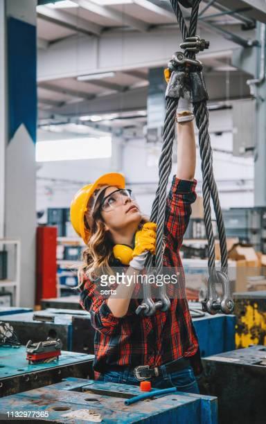 熟練した若い重工業のエンジニアの女性はクレーンホックボタンを握る安全作業服と働くことおよび工場の倉庫の巨大な金属の構造の目的を動かす。xxxl サイズ - 吊り上げる ストックフォトと画像