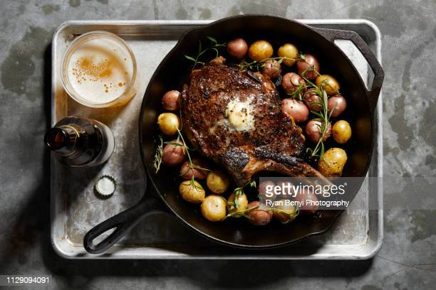 skillet with large tomahawk steak & potatoes, overhead view - food state stock pictures, royalty-free photos & images