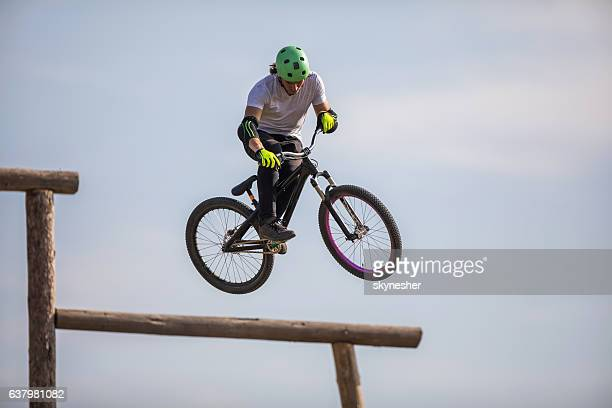 Skillful cyclist jumping high up against the sky.