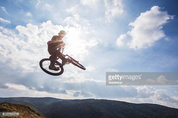 Skillful freestyle cyclist doing whip negative trick against the sky.