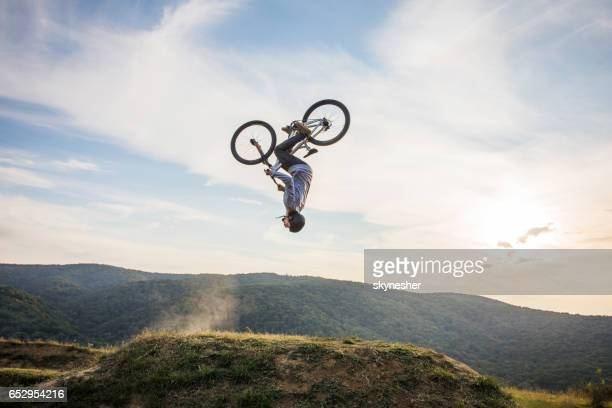 skillful man on bicycle performing backflip in nature. - acrobatic activity stock photos and pictures