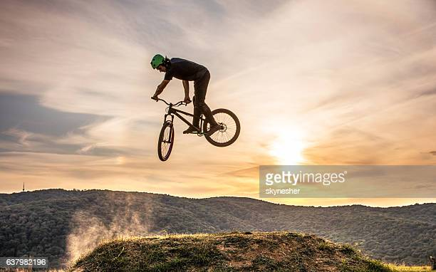 Skillful man on mountain bike practicing 360 xup at sunset.