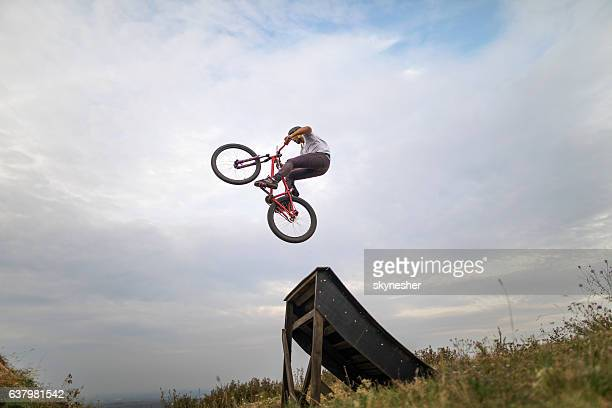 Skillful mountain bike cyclist performing straight air jump.
