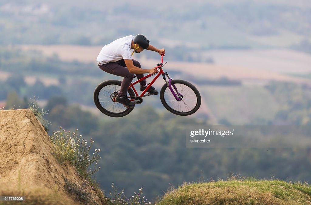 Skillful Mountain Bike Rider Jumping Over Dirt Hills Stock