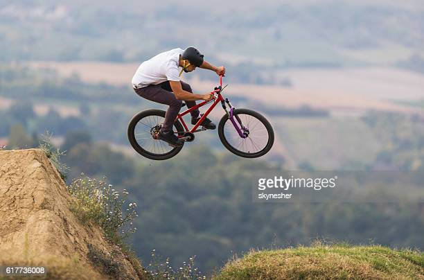Skillful mountain bike rider jumping over dirt hills.
