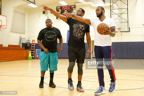 NBA skills trainer Stanley Remy talks with Dwyane Wade of the Miami Heat and John Wall of the Washington Wizards during NBA Offseason training with...