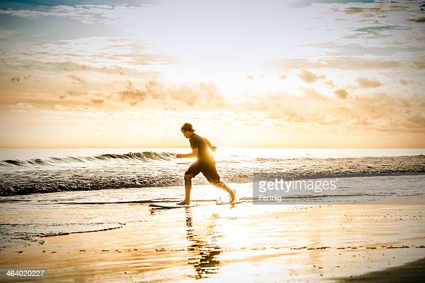 skim boarding at sunset on a beach - outer banks stock pictures, royalty-free photos & images